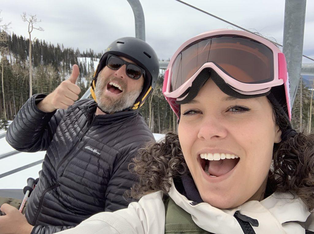 man and woman on ski lift waving at camera