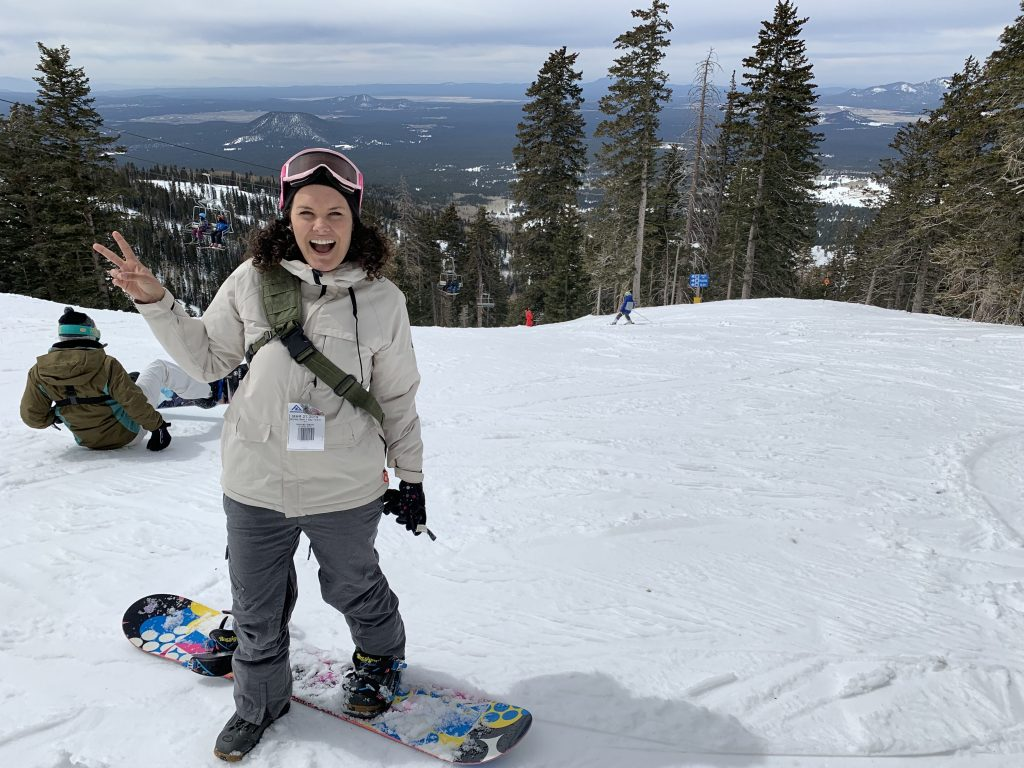 woman standing on snowboard on side of snowy mountain