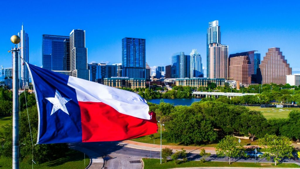 Texas flag in foreground of view of Austin Texas skyline