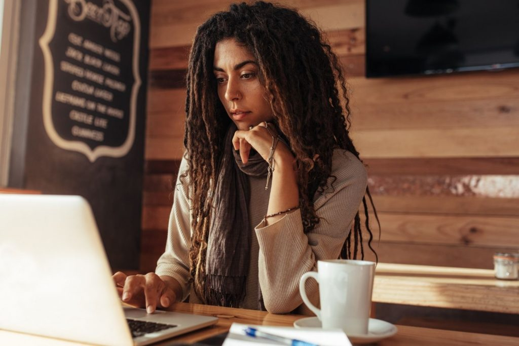 woman sits at table in coffeeshop working on a laptop with a cup of coffee next to her
