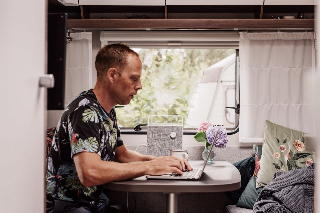 male freelance writer sits at RV table to work while surrounded by cozy home decor with a view of the outdoors over his shoulder
