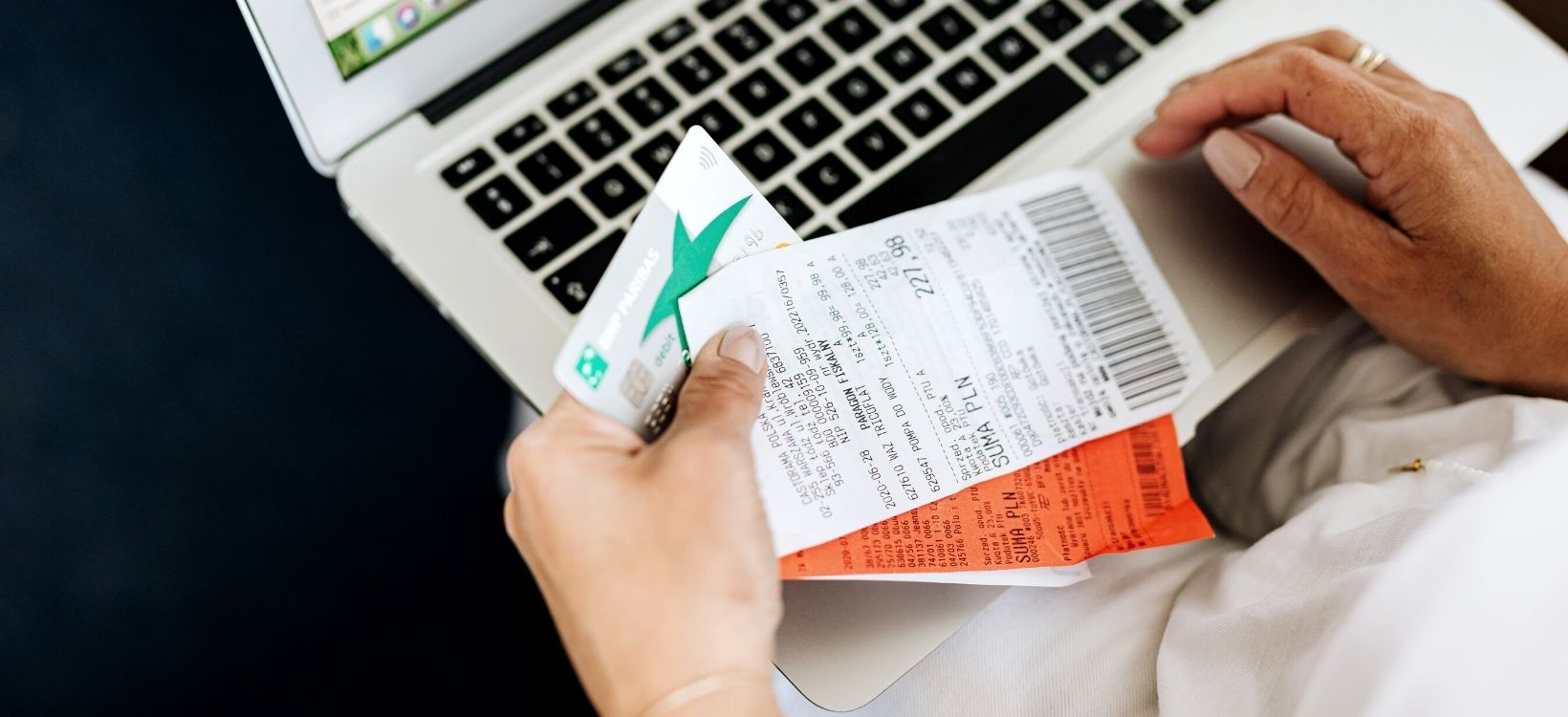 Person sits with laptop, sorting through receipts to prep for taxes